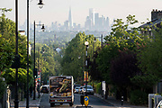 With the London skyline in the far distance, tesco delivery van descends the steep gradient of Gypsy Hill in Crystal Palace, on 16th June 2021, in London, England.