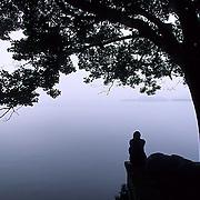 China, People, Person meditating at West Lake near city of Hangzhou.