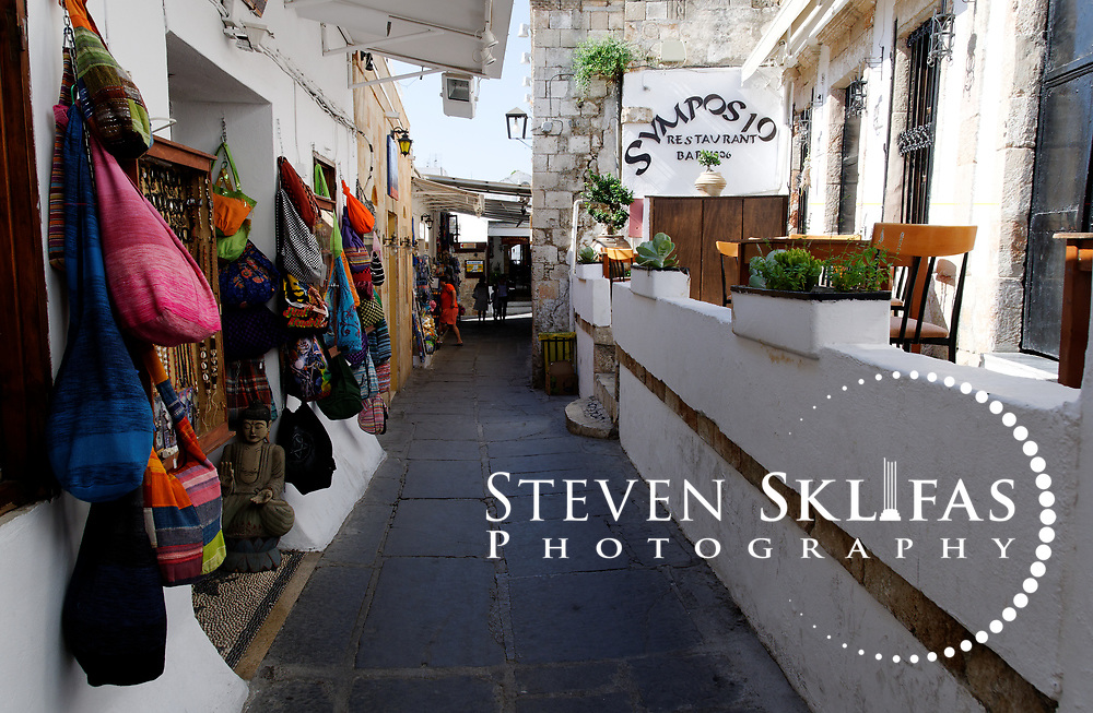 Rhodes. Greece.  View of one of the many gift shops selling traditional and imported souvenirs, handicrafts and clothing in Lindos. Laying on the slopes of the dramatic Acropolis and Knights castle, the dazzling medieval whitewashed village of Lindos is a maze of narrow winding black and white tiled alleyways fronted by imposing doorways which lead to flower filled courtyards of the unique Lindian houses which were built by rich sea-captains during the 15th  and 18th century's. Lindos is located on the east coast of the island of Rhodes which is the largest of the Dodecanese Island group and one of the most popular Greek Islands.