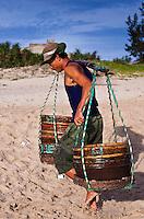 Man carrying baskets of fish on China Beach, Vietnam.