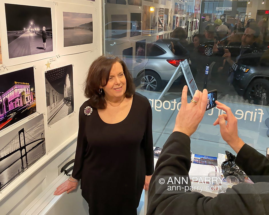 Huntington, New York, U.S. February 29, 2020. Susan Tiffen poses under her photo 'Jones Beach Babe,' a Best in Show co-winner, as her son takes her picture during reception at fotofoto Gallery for its 'Your Best Shot' Open Photography push-pin exhibition.