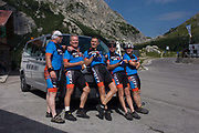 A group of cycling mates gather for a photo on the Passo Falzarego (Pass) in the Dolomites, south Tyrol, Italy. Cyclist groups as well as biker clubs ascend the pass (alt 2.105m) as part of their tours of the Dolomites - one of the must-do climbs on two and four wheels. The Falzarego Pass is a high mountain pass in the province of Belluno in Italy and connecting Andráz and Cortina d'Ampezzo. The name Falza Rego means false king in ladin and refers to a king of the Fanes, who was supposedly turned to stone for betraying his people.