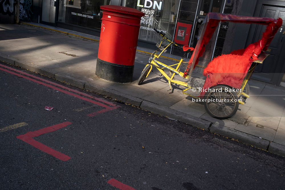 Parked at the kerbside on the Commecial Road Red Route in afternoon sunlight, are a red rickshaw vehicle and alongside, a red Royal Mail postal box on 21st October 2021, in London, England.