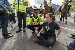 September 9, 2017 - London, UK - London, UK. 9th September 2017 Police threaten a woman sitting on the road at the Festival of Resistance against DSEI Arms Fair to block lorries entering with arms with arrest. The Defence & Security Equipment International, backed by the UK government, is where arms companies and arms dealers sell weapons to countries around the world including many repressive regimes. The road at the East Gate was blocked by a lock-on by two protestersand others including this group sat on the road in front of it, with a large group holding a Quaker meeting. Police tried to clear the road and made several arrests including the two involved in the lock-in and another who lay under the wheels of the lorry.  Peter Marshall Images Live (Credit Image: © Peter Marshall/ImagesLive via ZUMA Wire)