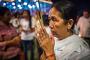 02 FEBRUARY 2013 - PHNOM PENH, CAMBODIA:  A Cambodian woman prays for former King Norodom Sihanouk at a small shrine near the Royal Palace. Much of Phnom Penh has been shut down to honor former King Norodom Sihanouk, who ruled Cambodia from independence in 1953 until he was overthrown by a military coup in 1970. Only bars, restaurants and hotels that cater to foreign tourists are supposed to be open. The only music being played publicly is classical Khmer music. Sihanouk died in Beijing, China, in October 2012 and will be cremated during a state funeral royal ceremony on Monday, Feb. 4.    PHOTO BY JACK KURTZ