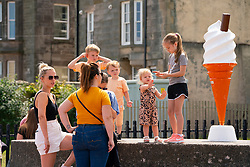 Portobello, Scotland, UK. 24 June, 2020. With sunshine and temperatures of 24C , the beach and promenade at Portobello outside Edinburgh were busy with the public who were enjoying the freedom of a relaxation of the covid-19 lockdown. Ice cream van had large cone to attract customers. Iain Masterton/Alamy Live News