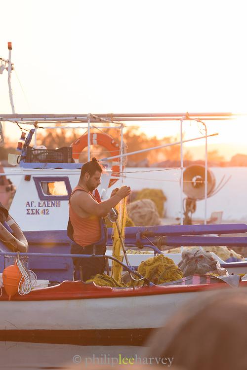 Side view of fisherman on boat moored in harbor at sunrise, Skala Kallonis, Lesbos, Greece