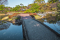 """Stone Bridge at Ninomaru Imperial Palace East Gardens -made up of the Honmaru and Ninomaru areas of Edo Castle.  None of the Edo Castle buildings remain today, though the moats, walls, gates and guardhouses still exist.  Honmaru is the most spacious area of the garden and visitors can view cherry trees, roses, bamboo and a tea garden.  Ninomaru Garden is planted with 260 trees donated by each prefecture of Japan surrounding a pond.  In 1963 the garden was declared by the Japanese government a """"Special Historic Relic"""" under Cultural Properties Protection."""