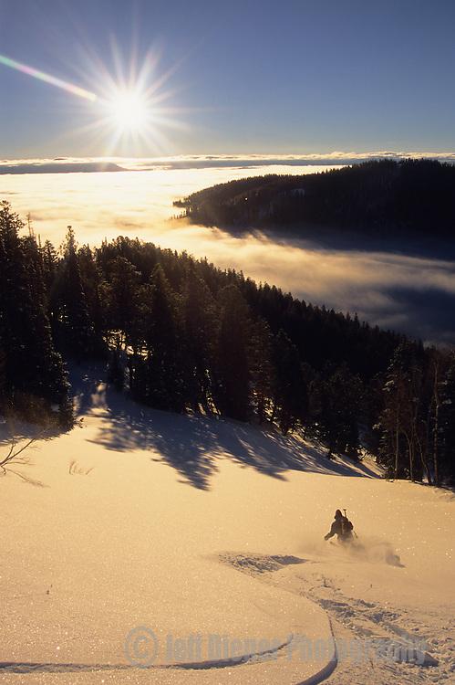 A backcountry skier makes turns through powder snow on Teton Pass in Jackson Hole, Wyoming.