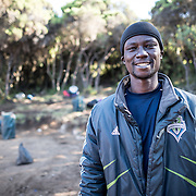 A porter poses for a photo at Mweka Camp on Mt Kilimanjaro.