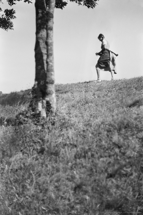 Girl walking on hilltop with trees, Molln, Austria, 1935