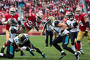 San Francisco 49ers running back Matt Breida (22) attempts to leap over the Jacksonville Jaguars defense at Levi's Stadium in Santa Clara, Calif., on December 24, 2017. (Stan Olszewski/Special to S.F. Examiner)