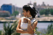 Iris Garcia Costa poses at one of the myriad locations a photographer takes her for her fifteenth birthday photo shoot. The traditional 15th birthday coming-of-age party for young girls is called a Quinceañera. The Costa's live in the Marianao district of Havana, Cuba.  From coverage of revisit to Material World Project family in Cuba, 2001.