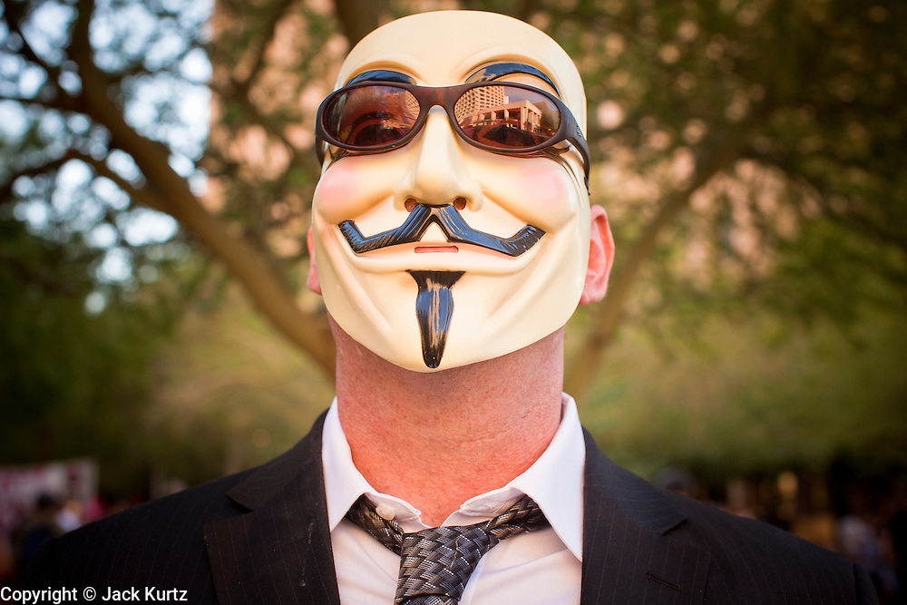"""16 OCTOBER 2011 - PHOENIX, AZ: An Occupy Phoenix protester with a Guy Fawkes mask from the movie """"V for Vendetta"""" in downtown Phoenix, AZ, Sunday. The Guy Fawkes mask has become the most visible sign of the Occupy movement. About 200 people continued the Occupy Phoenix protest in downtown Phoenix Sunday afternoon. The protest peaked Saturday afternoon at about 2,000 people. Nearly 50 people were arrested late Saturday night on misdemeanor trespassing charges when they tried to camp in a park near downtown and on Sunday the crowd dwindled to 200. Protesters hope to continue the protest through Monday by marching around downtown and picketing banks in the area.    PHOTO BY JACK KURTZ"""