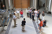 Circular winery vat hall, stainless steel fermentation tanks, a group of visiting wine enthusiasts, Laurent Cogombles, owner and winemaker, Chateau Bouscaut Cadaujac. Graves, Pessac Leognan Bordeaux France