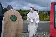 """Extinction Rebellion Penitents getting ready to protest for climate change at Truro Cathedral in Cornwall at 11am on the 28th of August 2020 in Truro, United Kingdom. Based on the medieval idea of repenting transgressions against your community by wearing sackcloth and ashes whilst bearing your """"sins"""" around your neck. The Penitents performed in total silence in this highly visual ceremony. Starting at the Truro Park and Ride they travelled into Truro and walked in procession through the town before carrying out the ceremony. These protests are highlighting that the government is not doing enough to avoid catastrophic climate change and to demand the government take radical action to save the planet.<br /> <br /> Extinction Rebellion is a climate change group started in 2018 and has gained a huge following of people committed to peaceful protests. These protests are highlighting that the government is not doing enough to avoid catastrophic climate change and to demand the government take radical action to save the planet."""