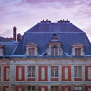 Sunset over front wing of Palace of Versailles, France
