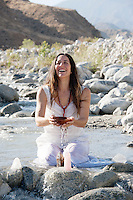 Spiritual woman laughing with joy in the flow of a wild river.She is holding an alms bowl with quartz and water receiving good vibrations and high frequency connection.