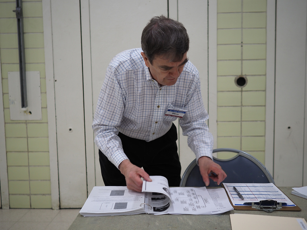 An Arlington, VA election official prepares to open the polls on Presidential Primary Day.
