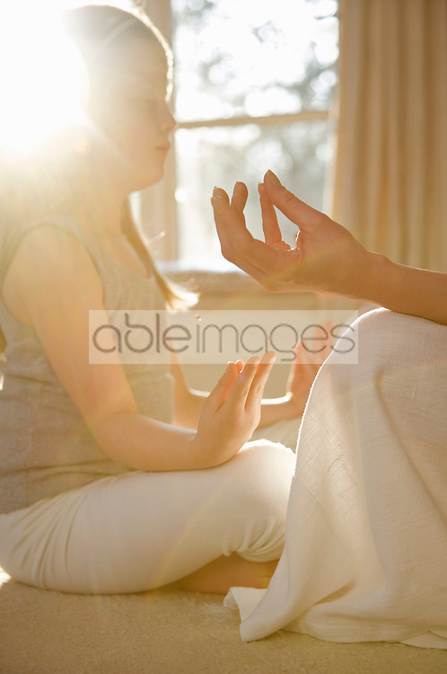 Close up of a young girl sitting in the cross legged opposite adult