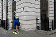 Outside the offices of BP, a businessman stretches tired leg muscles on 3rd February 2017, in St James's Square, London, England.
