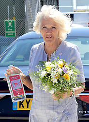 """The Duchess of Cornwall with gifts of Gin and flowers during a visit to Cornwall Air Ambulance Trust's base in Newquay to launch the new """"Duchess of Cornwall"""" helicopter, while on a three day visit to Cornwall with the The Prince of Wales."""