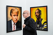 New York, NY - 5 May 2017. The opening day of the Frieze Art Fair, showcasing modern and contemporary art presented by galleries from around the world, on Randall's Island in New York City. A visitor flanked by two photographic portraits by Andres Serano, of Donald Trump, 2004, and Snoop Dogg, 2002, in Galerie Nathalie Obadia.