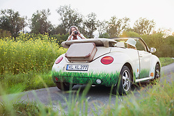 Man photographing woman in a car Beetle Cabrio, Bavaria, Germany
