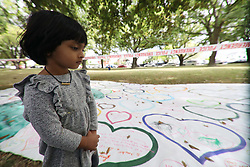 March 17, 2019 - Christchurch, New Zealand - A little girl walks past a banner with tribute messages to victims of the mosque attacks outside the Masjid Al Noor mosque in Christchurch on March 16, 2019. At least 49 people dead and more than 40 people injured following attacks on two mosques in  Christchurch. The national security threat level has been increased from low to high for the first time in New Zealand's history after this attack. (Credit Image: © Sanka Vidanagama/NurPhoto via ZUMA Press)