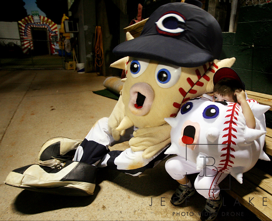 """Whit Rucker, 4, also know as """"Little Blowie,"""" collapses next to Columbia Blowfish mascot Blowie, following their dance performance to """"Jump On It"""" during the seventh inning of a Blowfish baseball game.  """"He's been Little Blowie for two years, and it was just kind of a fluke thing that it started,"""" says Whit's mom, Stacia Rucker. """"He just started in the stands dancing.  Then we made a costume one day and it didn't even have spikes on it, it was just a ball."""" Photo by Columbia, SC, photojournalist Jeff Blake"""