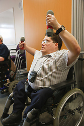 Using weights at exercise class for wheelchair users at Day Centre.