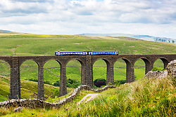 © Licensed to London News Pictures. 12/06/2018. Stonehouse UK. A commuter train crosses over the Arten Gill viaduct in the Yorkshire Dales today. Arten Gill viaduct was built as part of the Settle & Carlisle Railway between 1870-1875 by Victorian engineer John Sydney Crossley & constructed using Dent Marble, it has eleven arches & spans 201 metres. Photo credit: Andrew McCaren/LNP