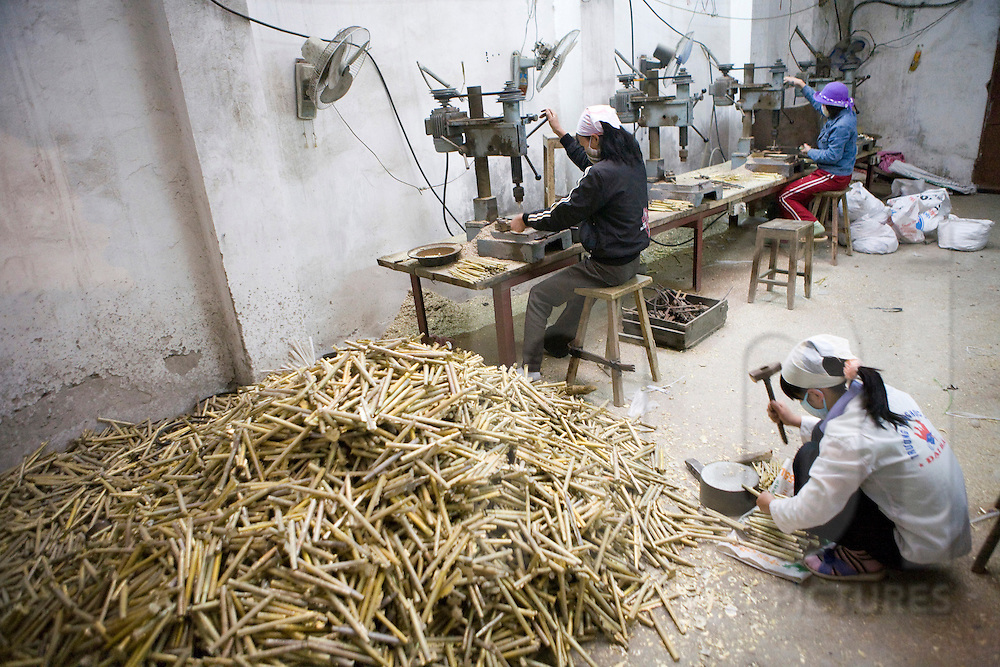 Color film photograph of a worker hammering an abundance of metallic pieces in a workshop of Dai Bai bronze casting craft village, Bac Ninh Province, Hanoi outskirts, Vietnam, Southeast Asia