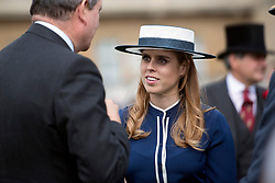 Princess Beatrice talks to guests during a garden party at Buckingham Palace in London.