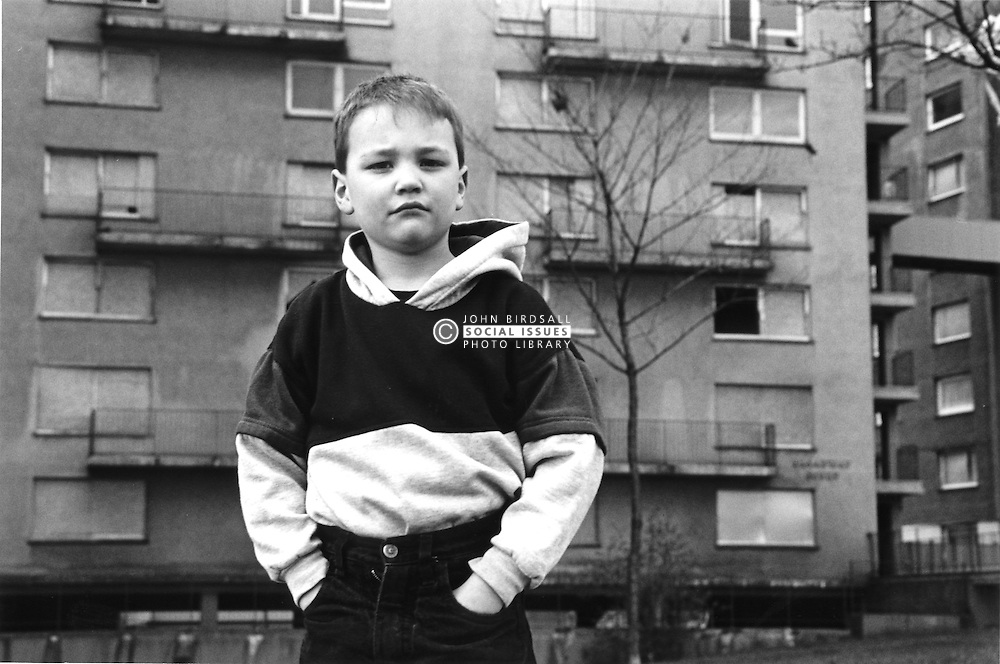 Portrait of young boy standing in front of derelict block of flats; looking serious,