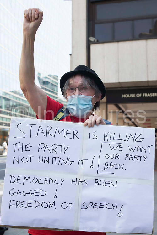 A woman holds a sign critical of Sir Keir Starmers leadership of the Labour Party during a protest lobby outside the partys headquarters by supporters of left-wing groups on 20th July 2021 in London, United Kingdom. The lobby was organised to coincide with a Labour Party National Executive Committee meeting during which it was asked to proscribe four organisations, Resist, Labour Against the Witchhunt, Labour In Exile and Socialist Appeal, members of which could then be automatically expelled from the Labour Party.