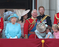 (left to right) Queen Elizabeth II, Duchess of Sussex, Prince of Wales, Duke of Sussex, Duchess of Cambridge holding Princess Charlotte and Savannah Phillips on the balcony of Buckingham Palace, in central London, following the Trooping the Colour ceremony at Horse Guards Parade as the Queen celebrates her official birthday.