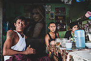 Mawlamyine, Myanmar - October 24, 2011: Patrons at a small restaurant in Mawlamyine, capital of Myanmar's Mon State. One patron's shoulder carries a tattoo of Che Guevara.