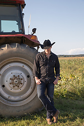 hot cowboy leaning on a tractor at sunset