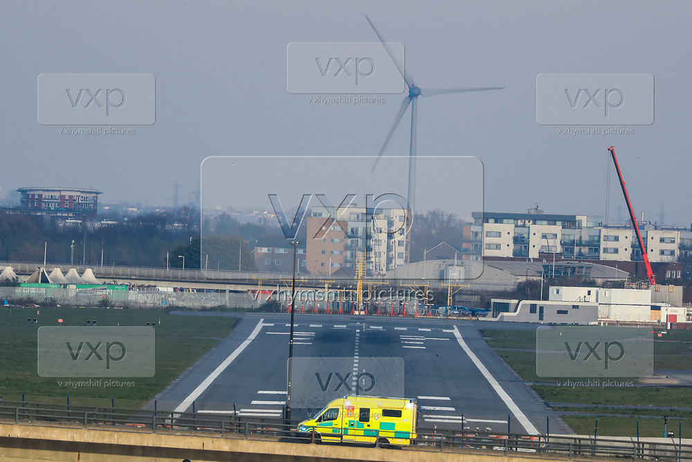 An NHS Ambulance is seen over a Bridge overviewing City Airport runway in London on Thursday, March 26, 2020. the airport is closed till at least the end of April. The airport is next to the ExCel Centre and may be used to help with logistics as the British Government announced Tuesday, that the ExCel Center in east London will become a 4,000-bed temporary hospital to deal with future coronavirus patients, to be called NHS Nightingale. (Photo/Vudi Xhymshiti)