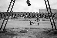 Three boys exercise on an athletic field adjacent to the Monumento a Calixto Garcia (not pictured) in Havana, Cuba