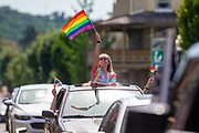 A woman standing through a sunroof waves a pride flag during the Mifflinburg Pride Event.