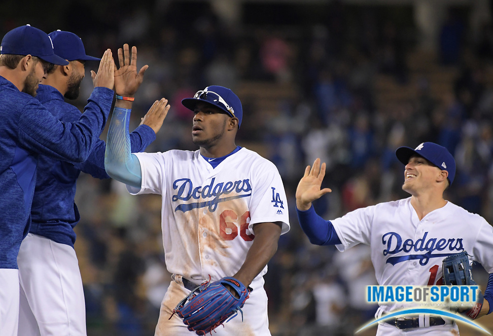 Apr 1, 2018; Los Angeles, CA, USA; Los Angeles Dodgers right fielder Yasiel Puig (66) and center fielder Kike Hernandez (14) celebrate with pitcher Clayton Kershaw and left fielder Matt Kemp after a MLB baseball game against the San Francisco Giants at Dodger Stadium.The Dodgers defeated the Giants 9-0.
