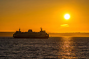 A Washington State Ferry crosses Puget Sound from Kingston to Edmonds as the sun prepares to set in this view from the fishing pier in Edmonds, Washington.