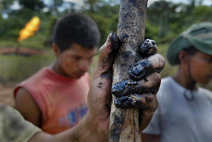 Close to his home Guillermo Grefa holds a long stick which he used to poke through the ground to expose the oil saturated soil beneath the site in Rumipamba in Eastern Ecuador. Guillermo is the son-in-law to Maria Aguinda, the person a suit is named for against Chevron/Texaco. In the background gas is burn't from a nearby oil field. They live very close to the polluted site. In the background are family members of Maria. They are all part of the Kichwa tribe.