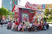 Workers sit in the shade at lunchtime in front of Coca Cola advertising in Shanghais popular Xiang Yang Fashion Market in Shanghai, China. It is possible to see from their older style clothes that they are either poor Shanghainese, or migrants from outside Shanghai. The advertising and these people shows the stark contrasts between old China and western modern China, and the gap between rich and poor.