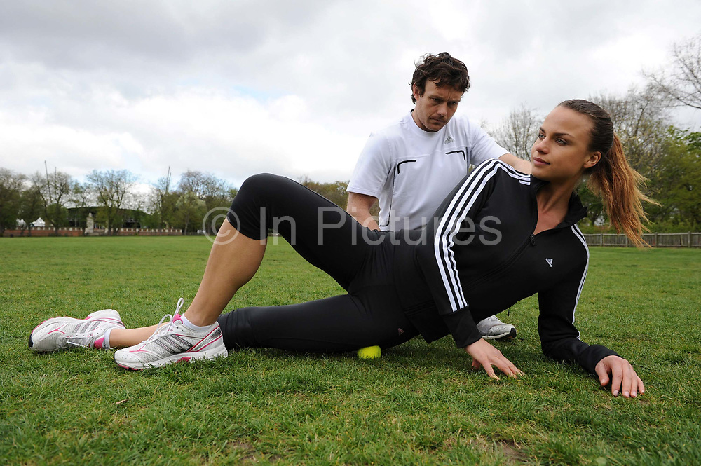 A woman with her personal trainer, exercising in a park in London, UK. Fitness, exercise and wellbeing has never been more popular in the United Kingdom as people strive to live healthy lives. Massaging muscles with a tennis ball.