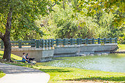 People Sitting on the Grass Next to the Lake at Mason Park