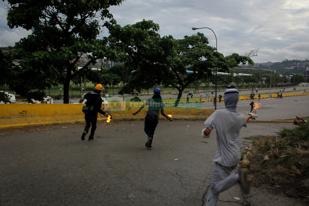 A group of opposition supporters throw Molotov bombs at the Bolivarian National Guard during a demonstration against President Nicolas Maduro in Caracas, Venezuela on May 1, 2017.