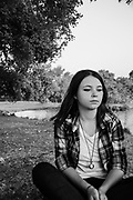 moody image of a young 25 year old woman alone in a park